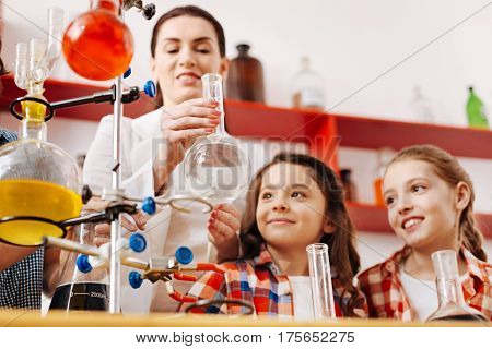 Being interested. Positive cute smart girls looking at the flask and smiling while attending scientific club meetings