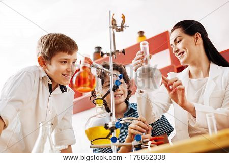 Lets start an experiment. Cheerful attractive positive teacher smiling and showing her students a chemical flask while starting their experiment