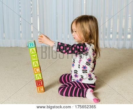 Young female toddler knocking over a tower of wooden blocks at home spelling Obamacare