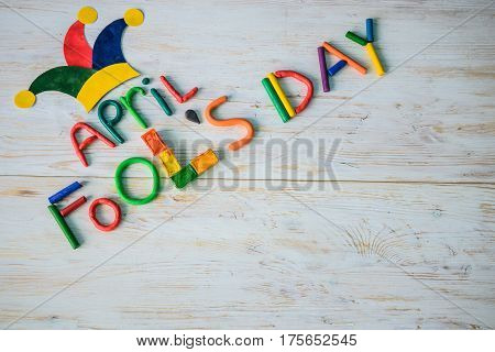 April Fools' Day text made with plasticine on white wooden background