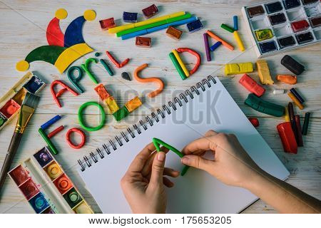 hands make April Fools' Day text made with plasticine on white wooden background