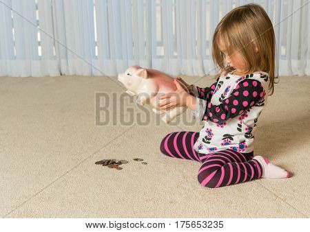 Young girl on floor of home trying to get money to pay off debt  out of a piggy bank for expenses in the future