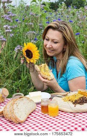 Smiling woman eating a honey bread in a meadow