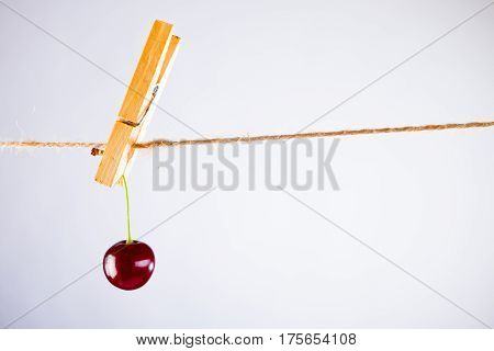 Red Cherry and rope on white with clamp fruit concept - desert, food