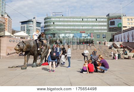 Oslo Norway - September 16 2016: A group of young people around and tw sitting on the sculpture Tiger (Tigeren) made by Elena Engelsen at tbe square Jernebanetorget in downtown Oslo.