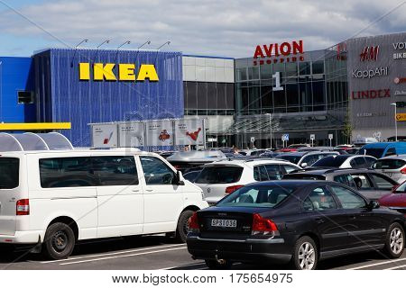 Umea Sweden - July 18 2016: Parking space with parked cars infront of the shopping center with Ikea furniture store and the shopping mall Avion.
