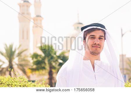 arabian man standing in front of mosque