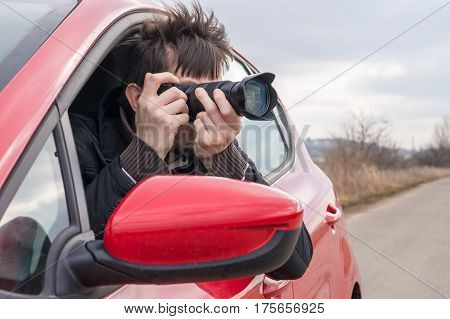 Paparazzi Is Taking Photo With Camera From Car.