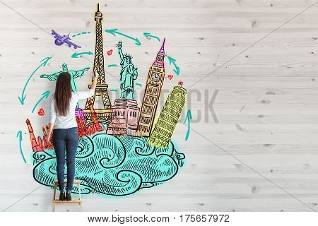 Back view of young woman standing on stool and drawing creative travel sketch on wooden wall. Tourism concept