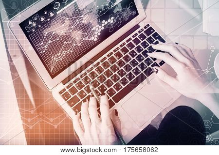 Top view of female hands using laptop with business charts on screen. Online marketing concept. Filtered image