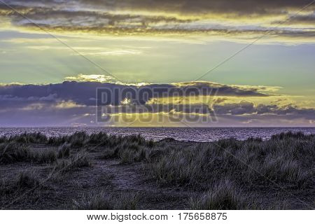 Sunset on the horizon from an island view. Marram grass covers the sandy shore. Cool evening on the coast.