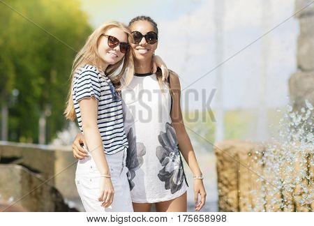 Teenagers Concepts and Ideas. Two Teenage Girfriends Together. Posing Against Fountain in Park Outdoors. African American Model and Caucasian Blond Model.Horizontal Image
