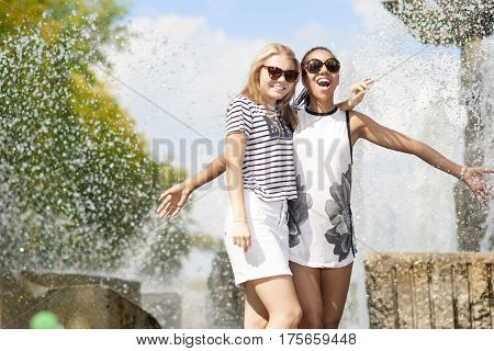 Teenagers Concepts. Two Funny and Laughing Teenage Girfriends Embracing Together. Posing Against Fountain in Park Outdoors. African American Model and Caucasian Blond Model.Horizontal Image Composition