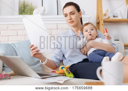 Able to succeed in both. Focused confident young mother perusing some data for her business while having time looking after her daughter during maternity leave