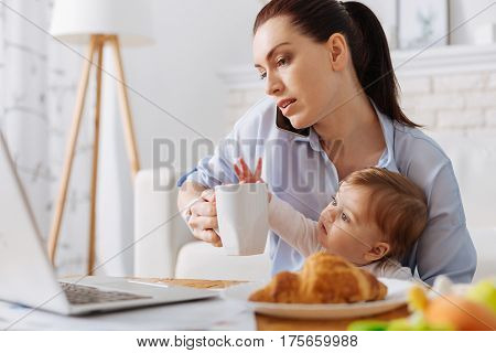 Using every free minute. Hardworking serious young mother calling someone while having a morning coffee and holding her child on her lap
