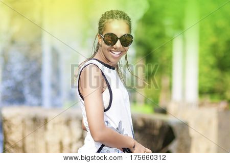 Teenager Lifestyle Concepts. Happy Smiling Young African American Teenager Girl With Plenty of Dreadlocks Posing in Park Outdoors. Horizontal Image Orientation