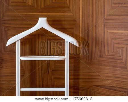Wooden hanger stand on brown wooden background