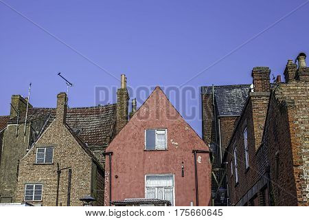 Old town house roof tops includiing red cement rendered building. Rear of run-down red-brick and renderd homes against a blue sky.