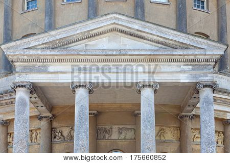 Ionic classical order of columns architecture with Roman relief mural sculpture in background.