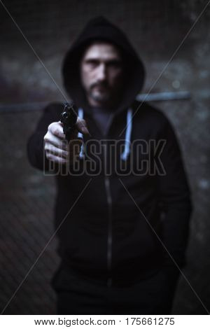 Give me your money. Attacking scary dangerous criminal holding a weapon in his hand and pointing it in the camera while wearing a black hoodie