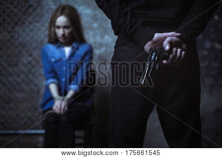 Let us have a conversation. Defenseless captured blonde lady sitting in a dark room being captured by a stranger who holding a gun