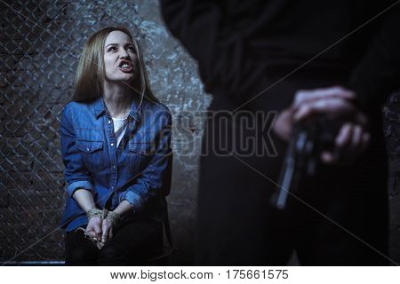 Not gonna get anything. Young strong unafraid lady shouting at a man who keeping her hostage and holding a gun behind his back