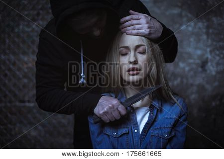Feel the blade. Raging antagonized mad man menacing a woman with a dagger while holding her by her head and leaning over her