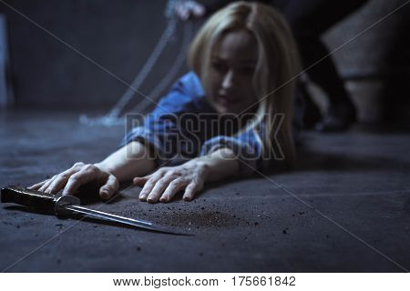 What are you trying to do. Defenseless persistent young woman making attempts taking a knife which lying on the floor near her while fighting off her abductor