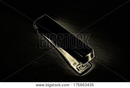 Stapler on a dark background is a necessary tool for the office serves to fasten documents paper among themselves