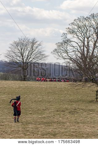 A lone Scottish piper in kilt and red uniform is running with bagpipes to join a Napoleonic battle reenactment