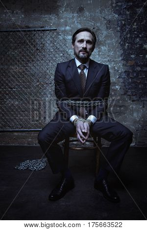 Is this some kind of joke. Influential rich powerful gentleman wearing a suit and sitting on a chair in a dark place while being chained