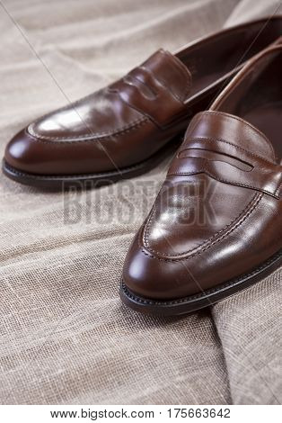 Shoes Concepts and Ideas. Closeup of Stylish Modern Brown Leather Penny Loafer Shoes On Mesh Surface.Vertical Image Orientation