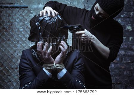 Why me. Scared exhausted captured businessman sitting with his hand tied and face covered with a plastic bag while abductor threatening him
