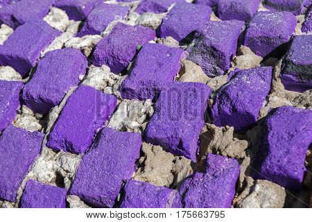 Vibrant purple bricks. An eroded lattice of brightly colored bricks forming an interesting abstract background pattern.