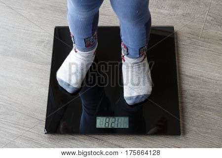yound boy legs on the scales - measure