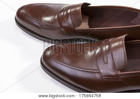 Footwear Concepts. Closeup of Pair of Stylish Brown Penny Loafer Shoes Against White Background. Above View. Horizontal Image