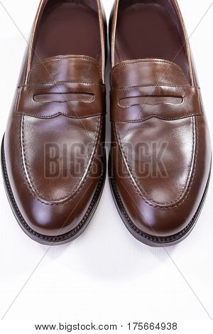 Footwear Concepts. Pair of Stylish Brown Penny Loafer Shoes Against White Background. Placed Together Closely. Vertical Image Composition