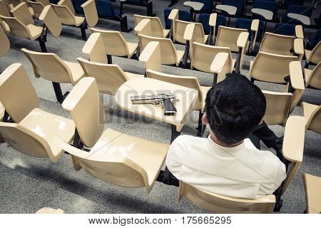 A man with a pistol in a lecture room / Armed campus concept