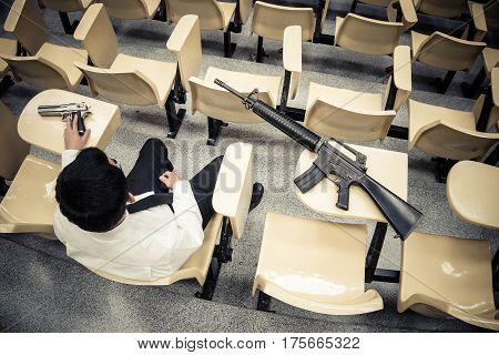 A man with a pistol and a rifle in a lecture room / Armed campus concept