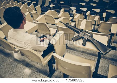 A man with a rifle in a lecture room / Armed campus concept