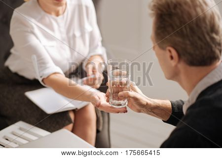 It is for you. Selective focus of a glass of water being held by a nice sympathetic pleasant therapist while being given to the patient