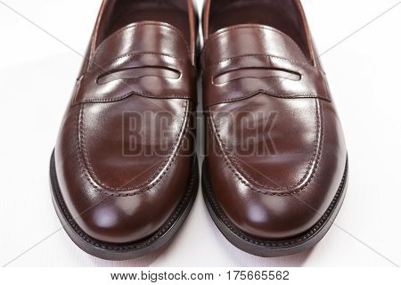 Footwear Concepts. Closeup of Pair of Stylish Brown Penny Loafer Shoes On White. Placed Together With Each Other. Horizontal Image