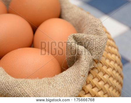 Brown Eggs in basket with homespun fabric close up. Shallow dof
