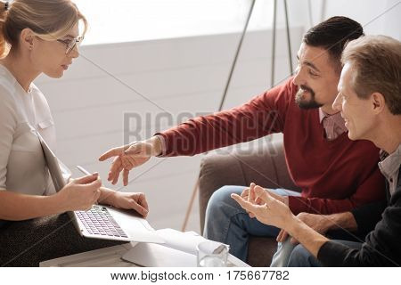 Explain this please. Positive bearded nice man stretching out his hand and pointing at the laptop screen while sitting on the sofa with his friend