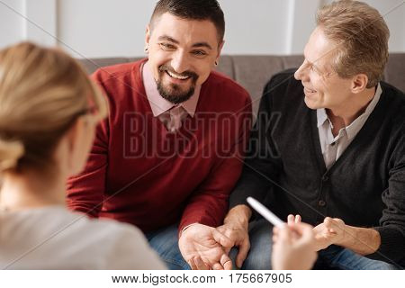 Positive emotions. Joyful delighted gay couple sitting together on the sofa and smiling while enjoying themselves