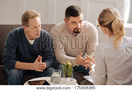 Advice from a psychologist. Sad depressed unhappy gay couple sitting on the sofa and listening to their psychologist while having a psychological session