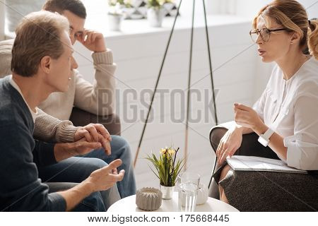Gender issues. Unhappy troubled mature man sitting with his boyfriend and talking to the psychologist while discussing their problems