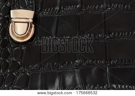 Close-up texture of black handbag from genuine leather with embossed under the skin of reptile, gold lock. Texture of background for the designer. For backdrop, substrate, use of composition. With place for your text.