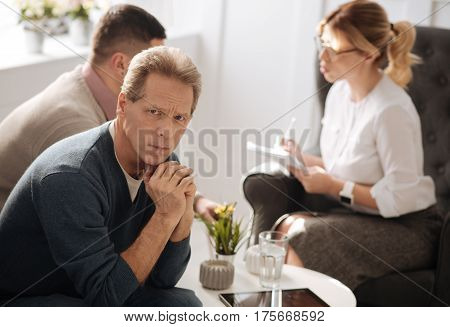 Being desperate. Unhappy troubled mature man clasping his hands and looking at you while being desperate