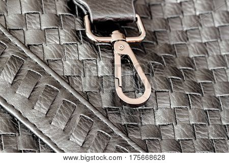 Texture of genuine dark wicker leather close-up and clasp, buckle of male handbag. Fashion background.